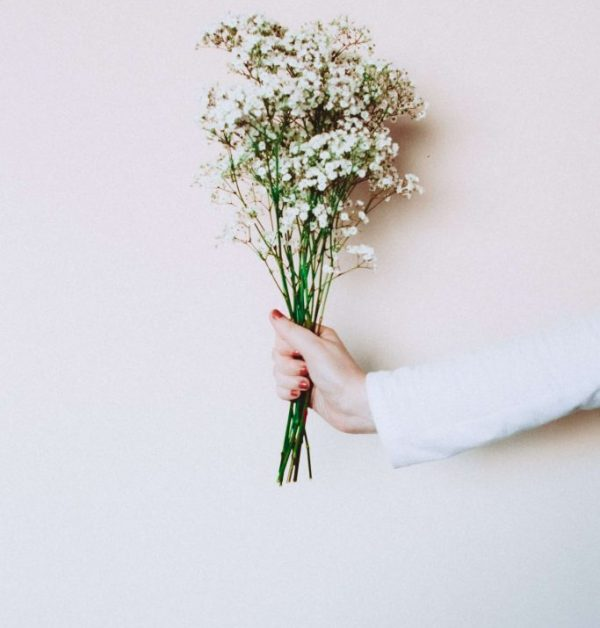 photo-of-woman-s-hand-holding-out-white-flowers-in-front-of-3147131 (1)